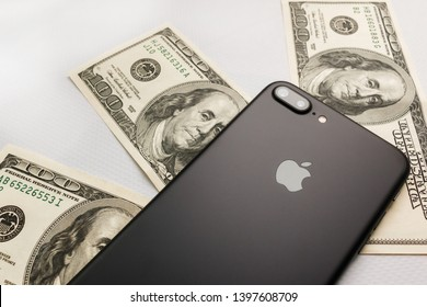 KYIV, UKRAINE - May 1, 2019: Black iPhone 8s plus on two hundred dollar bills. iPhone sales dropped concept. Apple still have issues selling iPhones. Slumping iPhone Sales concept
