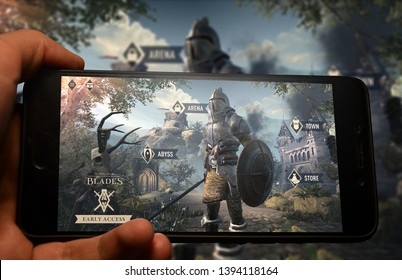 Kyiv, Ukraine; May 10, 2019: Hand holding phone with The Elder Scrolls Blades logo displayed in it with fluctuating graphic on background.