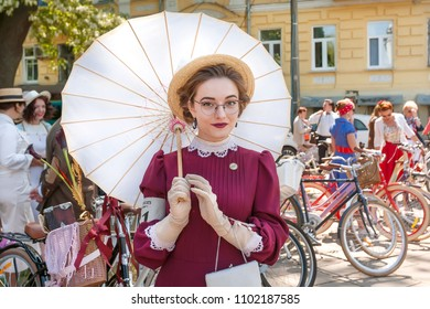 KYIV, UKRAINE - MAY 12, 2018: Young woman in old fashion dresses with umbrella chilling at festival Retro Cruise on May 12, 2018. Kiev is the 8th most populous city in Europe