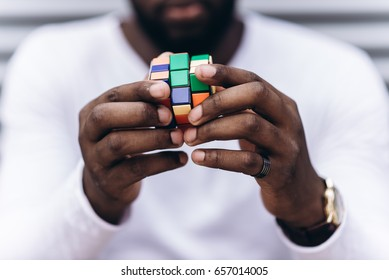 Kyiv, Ukraine - May 17th, 2017: Handsome Afro American man wearing casual clothes collect Rubik's Cube. Rubik's cube invented by a Hungarian architect Erno Rubik in 1974.