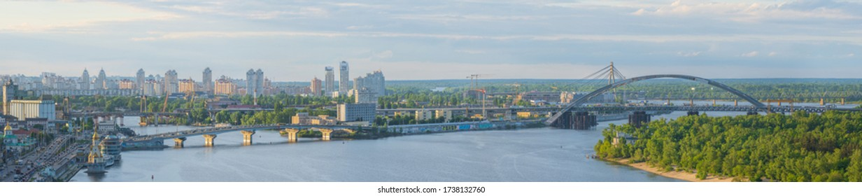 KYIV / UKRAINE - MAY 20, 2020: View of the embankment and bridges of Kiev from New Pedestrian and Bicycle Bridge in Kyiv, Ukraine