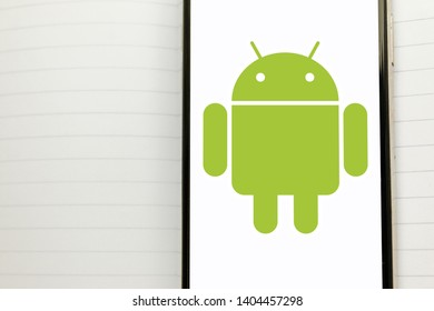 Kyiv, Ukraine – May 21, 2019: Android logotype on a white screen of the new modern smartphone. Huawei could lose access to Google apps/services
