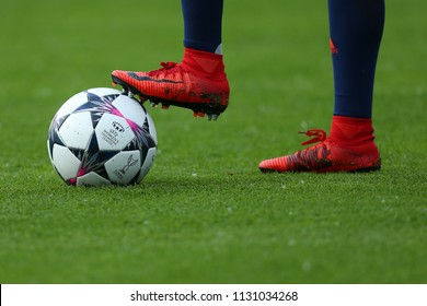 KYIV, UKRAINE - MAY 24, 2018: Close-up view of the UEFA Women's Champions League illustrative thematical photo. Match ball with red Nike boots of football player. Isolated at green grass background.