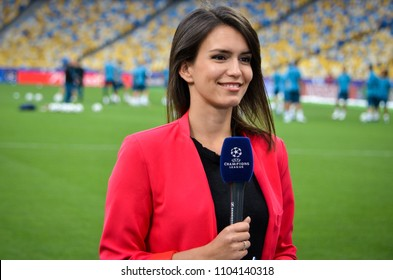 KYIV, UKRAINE - MAY 26, 2018: A very beautiful girl of a journalist with a microphone is preparing a reportage before the 2018 UEFA Champions League final match, Ukraine