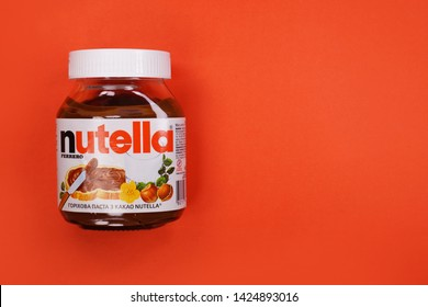 Kyiv, Ukraine - May 27, 2019: Nutella introduced to the market in 1964 by Italian company Ferrero. Nutella hazelnut on red background
