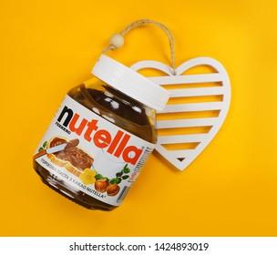 Kyiv, Ukraine - May 27, 2019: Nutella introduced to the market in 1964 by Italian company Ferrero. Nutella hazelnut on yellow background