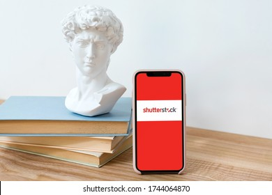 Kyiv, Ukraine - May 28, 2020: Shutterstock logo on Iphone X screen on wooden table with books and David head statue.