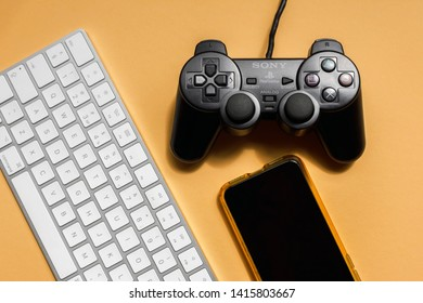 KYIV, UKRAINE - MAY 29, 2019: SonyPlayStation dualshock 2gamepad, white apple magic keyboard and iphone XS on the orange background, view from above.
