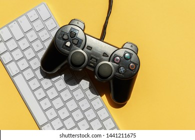 KYIV, UKRAINE - MAY 29, 2019: dualshock 2 controller, gray apple magic keyboard on yellow background, view from above. devices and gadgets for gamers