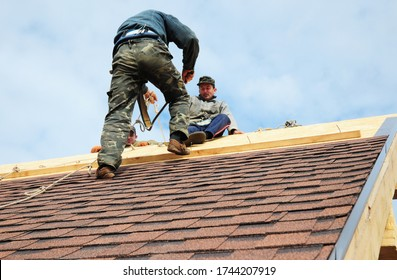 KYIV, UKRAINE - May, 29, 2020:  Roofing contractors with safety ropes, fall protection are finishing to install asphalt roof shingles on the roof ridge of the house roofing construction.