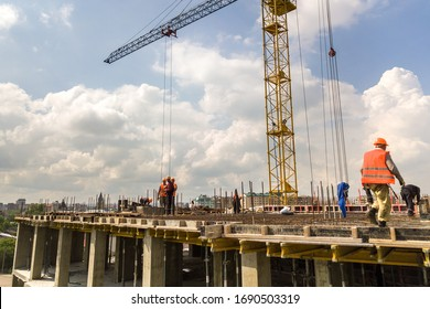 Kyiv, Ukraine - May 3, 2019: Workers working on concrete frame of tall apartment building under construction in a city.