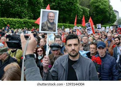 KYIV, UKRAINE - MAY 9, 2019: People hold pictures of World War Two soldiers as they take part in the Immortal Regiment march during the Victory Day celebrations in Kiev