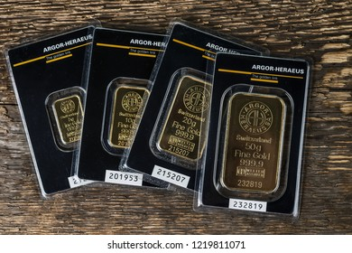 Kyiv, Ukraine - November 02, 2018: four small minted bars produced by the Swiss factory Argor-Heraeus - is one of the world's largest processors of precious metals. On a wooden background.