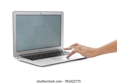 KYIV, UKRAINE - NOVEMBER 13, 2017: Woman using Apple MacBook Air Silver with empty screen on white background,  designed and developed by Apple Inc