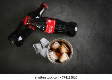 KYIV, UKRAINE - NOVEMBER 13, 2017: Glass of Coca-Cola with ice cubes and bottles on grey background