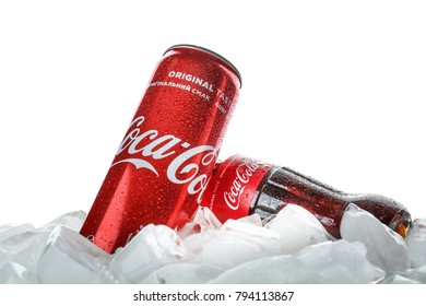 KYIV, UKRAINE - NOVEMBER 14, 2017: Bottle and can of Coca-Cola with ice cubes, isolated on white