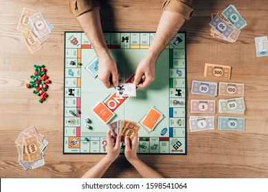 KYIV, UKRAINE - NOVEMBER 15, 2019: Cropped view of man holding explanation card and woman with toy currency while playing in monopoly game