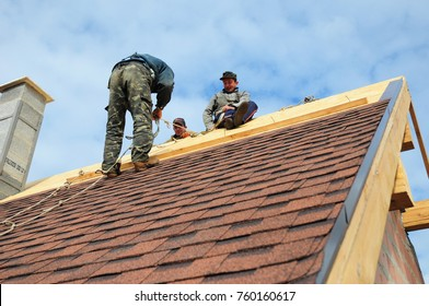 KYIV, UKRAINE - November, 22, 2017: Roofer laying asphalt shingles. Roofer with safety kit on the house roof installing, repair asphalt shingles.Roofing construction. Roofer's Kits for Fall Protection