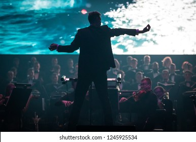 "KYIV, UKRAINE - NOVEMBER 22, 2018: Conductor of Symphony Orchestra Andrey Chernyi performs on stage during ""The Game of Thrones"" concert at National Palace of Arts ""Ukraina"" in Kyiv, Ukraine"