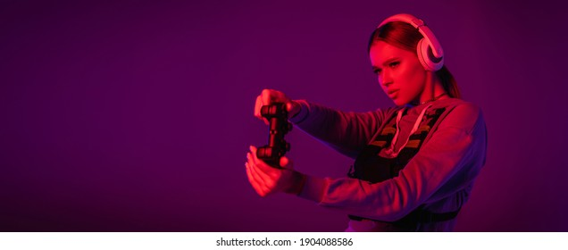 KYIV, UKRAINE - NOVEMBER 27, 2020: young woman in headphones playing video game on purple background, banner