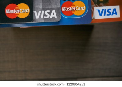 KYIV, UKRAINE - NOVEMBER 4, 2018: Close up shot of VISA and MasterCard bank cards with brown wooden background