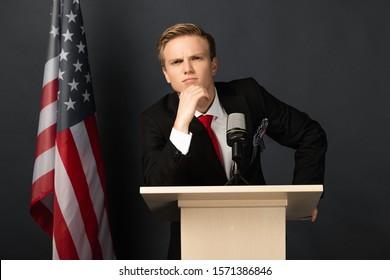 KYIV, UKRAINE - OCTOBER 18, 2019: thoughtful emotional man imitating Donald Trump on tribune with american flag on black background