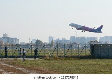 KYIV, UKRAINE - OCTOBER 19, 2019: People watch Wizzair Airbus A320-232 take off on the runway to Kiev airport