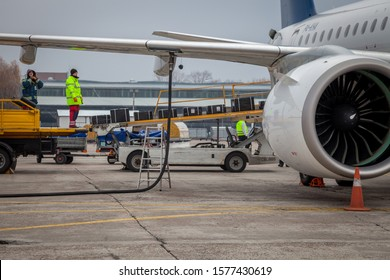 Kyiv, Ukraine - October 29, 2019: Refueling an airplane at an airport. The hose is connected to the wing.Air Astana airline plane is on the runway near the airport terminal. The plane Embraer E190-E2.