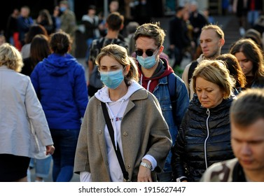 KYIV, UKRAINE- October  3, 2020: A woman and a man wearing a protective masks as a precaution against the outbreak of Coronavirus  walks down the street during the coronavirus crisis.