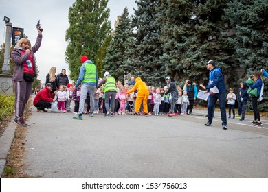 Kyiv, Ukraine - October 5, 2019: Children's street running competition.  A woman shoots a starting gun before the race. Little children are on the start line, getting ready to run.