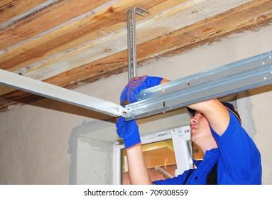 KYIV, UKRAINE - September, 05, 2017:  Metal roofing construction. Install metal roof. Contractor measure and install garage door opener.