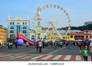 Kyiv, Ukraine - September 1, 2018: Ukrainians and tourists are walking at the festival on Kontraktova Square in Kyiv. Cityscape of Kyiv with Podil historic neighborhood and Ferris wheel.