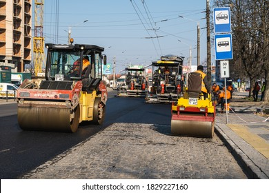 KYIV, UKRAINE - September 10, 2020: Heavy asphalt road roller with heavy vibration roller compactor that press new hot asphalt and asphalt paver machine on a road construction site on a street.