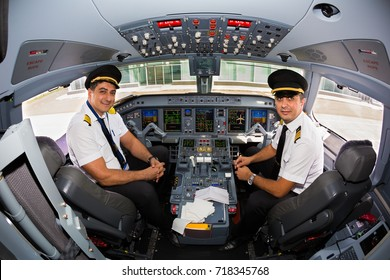 Kyiv, Ukraine - SEPTEMBER 12, 2017: Airline pilots at work in the cockpit. Embraer ERJ-190 cockpit. Airplane at the airport.