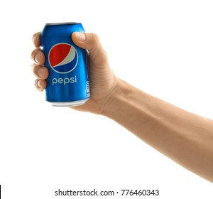 KYIV, UKRAINE - SEPTEMBER 18, 2017: Young man holding can of Pepsi on white background