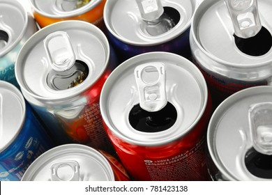 KYIV, UKRAINE - SEPTEMBER 18, 2017: Opened cans with drinks of different popular brands, closeup