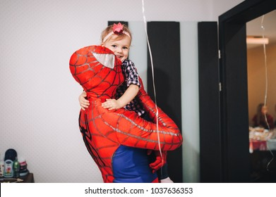 Kyiv, Ukraine - September, 2017. The spiderman is holding a little girl in his arms. A man in a spiderman suit came to congratulate the child on his birthday. Spiderman Costume Rental.