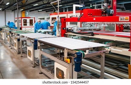 KYIV, UKRAINE - September 2019: production of solar panels, man working in factory. Closeup of special machinery at solar production panels factory. Industrial technic at plant. Modern green energy pr