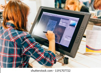 KYIV, UKRAINE - SEPTEMBER 22, 2018: Young woman or girl draws with Wacom tablet at Comic Con Ukraine convention at Kyiv or Kiev