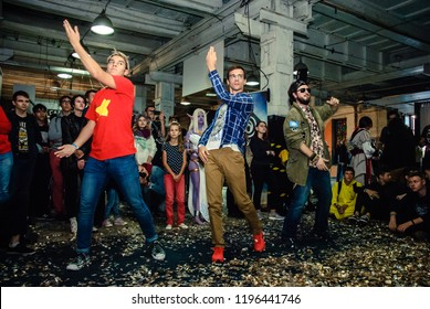 KYIV, UKRAINE – SEPTEMBER 23, 2018: Three young men dancing to the Just Dance a rhythm game by Ubisoft at ComicConUkraine, the first pop culture convention in Ukraine; editorial street photo
