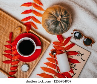 Kyiv, Ukraine - September 6, 2018: Autumn flatlay with cup of coffee, red plate on the wooden tray, gold spoon, candle, pumkin, sunglasses, book and red leaves.