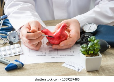 KYIV, UKRAINE-MARCH 8, 2018: At doctors appointment physician shows to patient shape of stomach with focus on hand with organ. Scene explaining patient causes and localization of diseases of stomach