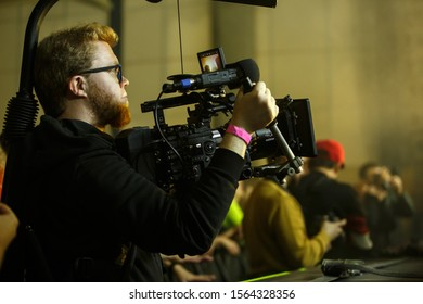 KYIV-17 NOVEMBER,2019:Videographer shoots concert with professional 5K Red Ranger videocamera mounted on stabilizer vest rig.Pro video camera man films music festival in night club using pro equipment
