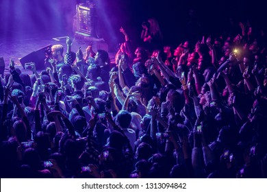 KYIV-2 FEBRUARY,2019: Concert crowd partying to the music in nightclub and take pictures with smartphones.Famous singer Suzanna fans wave hands on dance floor in club.Pop musical festival audience