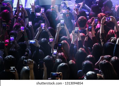 KYIV-2 FEBRUARY,2019:Concert crowd partying to dj music in nightclub,take pictures with smartphones in hand.Djs fans wave hands,shoot mobile photos on dance floor in club.Pop musical festival audience