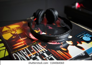 KYIV-28 JULY,2018: Retro hip hop music record with album of famous rap band Wu Tang Clan on table in studio. Pro DJ headphones for mixing music tracks