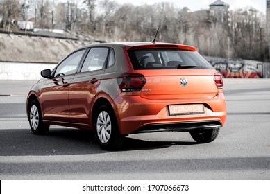 Kyiv/Ukraine - 04/14/2020: Orange Car Volkswagen Polo on the street. Look from the back with logo