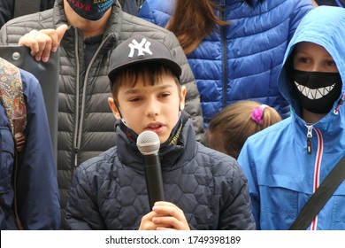 Kyiv/Ukraine - 05.29.2020: children with microphones speak at a protest political street rally. Their parents are in a large crowd of protesting people