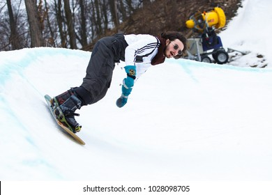 KYIV,UKRAINE-3 FEBRUARY,2018:Snowboard park Goloseev Ski Park opening.Downhill freeride competition athlete rides down the track from hill on snow board deck.Winter extreme sports
