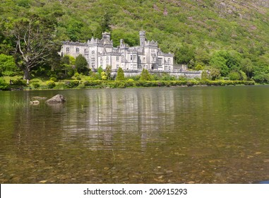 Kylemore Abbey with lake in foreground, in Ireland.